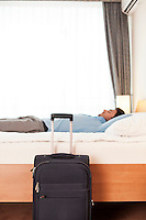Side view of young businessman sleeping in bed by luggage at hotel