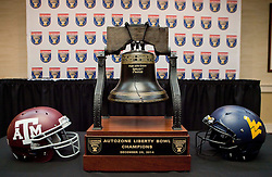 Helmets from Texas A&M and West Virginia are seen with the Liberty Bowl trophy before a press conference one day before the Liberty Bowl in Memphis, TN.
