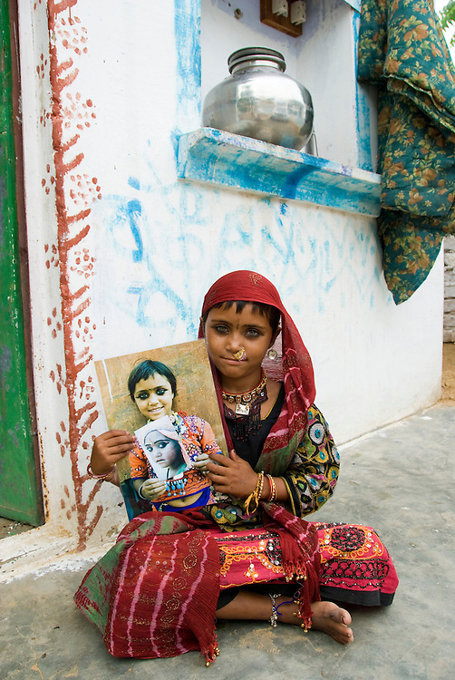 India (Rajasthan) - portrait of a village girl (gypsy) holding photographs taken of her when she was younger (by the same photographer, Mirjam Letsch).