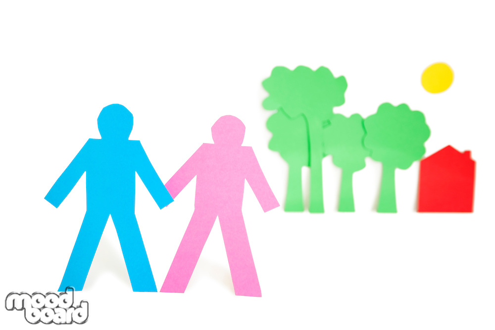 Paper cut outs representing a couple with trees and house over white background