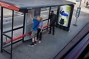 A man in blue reaches to point at his intended bus route at a bus stop featuring a reaching girl in school uniform, a return to school advert in Elephant & Castle in south London, on 29th August 2019, in Westminster, London, England.