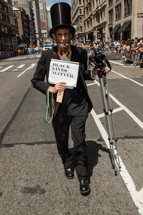 "New York, NY - 25 June 2017. New York City Heritage of Pride March filled Fifth Avenue for hours with groups from the LGBT community and it's supporters. A man dressed as Abraham Lincoln with a sign reading ""Black lives matter."""