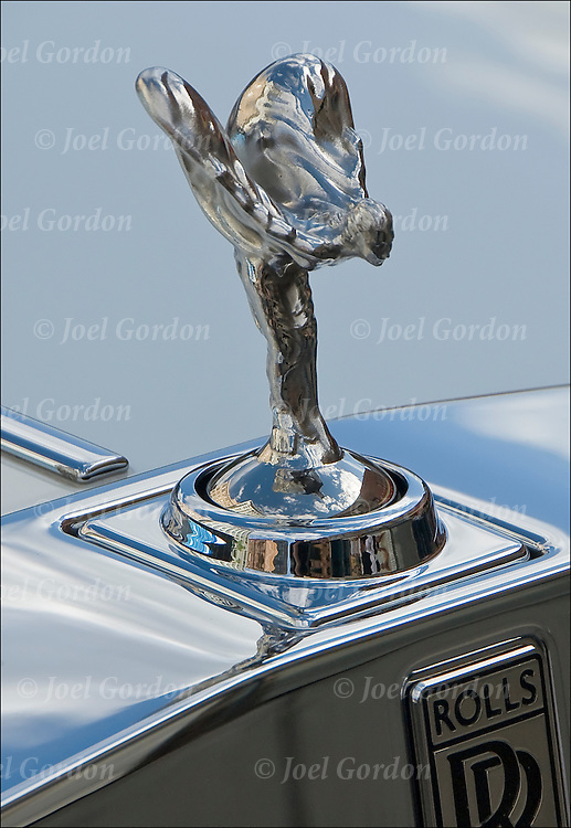 Rolls Royce symbol of wealth.   ..The Spirit of Ecstasy is the name of the hood ornament on Rolls-Royce cars. It is in the form of a woman leaning forwards with her arms outstretched behind and above her. Billowing cloth runs from her arms to her back, resembling wings.