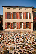 Cobblestone road and historic home on the battery at Adgers Wharf in Charleston, SC.