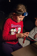 Molly demonstrates crocheting for a new friend  by lantern light at the Russell Pond Campground