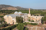 Isa Bey Mosque, built 1374-5, with the Ayaslug Hills in the distance, Selcuk, near Ephesus, Izmir, Turkey. The mosque was built in Seljuk style under the Emir of Aydin in honour of the Aydinid Isa Bey. Here we see the courtyard of the mosque with its Classical columns, the brick minaret, which is ruined above its balcony level, and the main building of the mosque with its 2 domes. Columns and stones from the ruins of the nearby Greek and Roman city of Ephesus and the Temple of Artemis were incorporated into the building's interior and exterior. The mosque was restored in 1934. Picture by Manuel Cohen