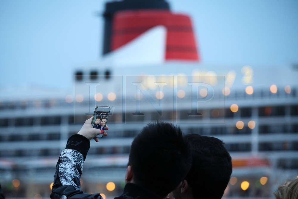 © Licensed to London News Pictures. 09/05/2014. Southampton, UK. Two people taking a 'selfie' with the iconic Cunard red funnel of the Queen Mary 2 in the background. Firework celebrations marking the 10-year anniversary of the Cunard flagship, Queen Mary 2, take place in the port of Southampton this evening, 9th May 2014. All 'three queens' of the Cunard fleet were present at the event, which included a 10-minute firework display, one minute for every year that the QM2 has been in service. Photo credit : Rob Arnold/LNP