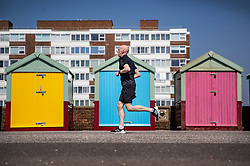 © Licensed to London News Pictures. 22/04/2019. Brighton and Hove, UK. A man runs past multi-coloured beach huts on the Western Esplanade at Hove, West Sussex. Most of the UK is enjoying record breaking high Easter weekend temperatures. Photo credit: Peter Macdiarmid/LNP