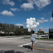 THURSDAY, FEBRUARY 15- 2018---PARKLAND, FLORIDA--<br /> A boy carries balloons to release outside Marjory Stoneman Douglass High School one day after a mass shooting with 17 casualties.<br /> (Photo by Angel Valentin/FREELANCE)