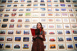 © Licensed to London News Pictures. 11/11/2019. London, UK. A staff member stands in front of a preview of 'Steve McQueen Year 3' exhibition at Tate Britain. An installation of over 3,000 class photographs on the walls of Tate Britain's Duveen Galleries, depicting more than 70,000 Year 3 pupils from London's primary schools by Turner Prize-winning artist and Oscar-winning filmmaker Steve McQueen. The exhibition opens on 12 November until 3 May 2020. Photo credit: Dinendra Haria/LNP