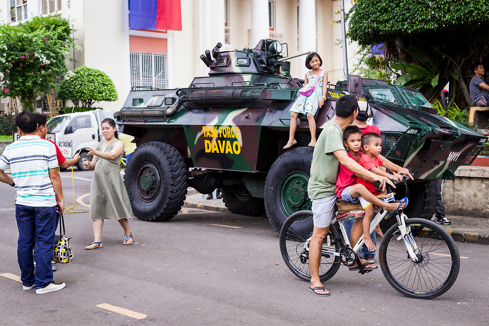 Davao City, Mindanao, Philippines - JUNE 18: A girl is seen posing on top of the Davao Task Force Army tank that stands by at Quezon Park near Davao City Hall.  Security in the city is tight since President Duterte implemented a Martial Law for 60 days in Mindanao due to the heavy fighting in Malawi 250km away.