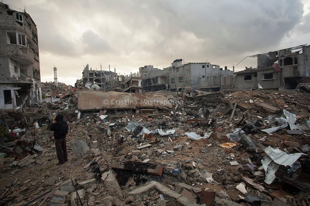 """Shejaya, quartiere a nord della striscia di Gaza. Una delle zone piu colpite dall'attacco israeliano """"Margine protettivo"""". Il quartiere è stato raso al suolo. La popolazione, a distanza di sei mesi dalla fine della guerra, vive tra le macerie della propria casa, al freddo, senza luce, gas e acqua. Nella foto la vista di una casa distrutta e una voragine provocata dalle bombe degli F16 israeliani. Dalla fine della guerra le macerie non sono state rimosse."""