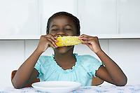 Girl (5-6) sitting at table eating corn cobb