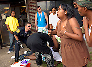 Bystanders react as a police officer provides emergency medical care to a teenage shooting victim in Hartford, Connecticut in August 2008. The shooting is believed to be a retaliatory attack by a rival teen gang. Eleven people were shot in three attacks on this August weekend in Hartford making it the most violent week of the year in the city. As a result of the weekend violence, a 90-day curfew was implemented and enforced by the police.