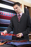 Businessman selecting tie in clothes store
