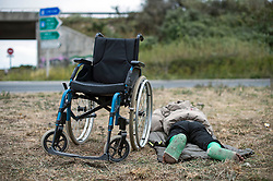 © Licensed to London News Pictures. 10/08/2015. Calais, France. A migrant who badly injured both legs while attempting to enter the Eurotunnel complex, lies by the roadside next to his wheelchair at the migrant camp in Calais.  Hundreds of migrants attempt to illegally access the Eurotunnel complex each night in order to board a train and reach the UK. Photo credit: Ben Cawthra/LNP