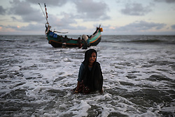 COX'S BAZAR, BANGLADESH - SEPTEMBER 13 : A Rohingya Muslim woman, fled from ongoing military operations in Myanmar's Rakhine state, gets off a boat while fleeing to a temporary makeshift camp, crossing Naf river, after crossing over from Myanmar into the Bangladesh side of the border, in Shah Porir Dwip near Cox's Bazar, Bangladesh on September 13, 2017. Rohingya Muslims pay local fishers 36 US Dollars in order to cross to Shah Porir Dwip peninsula. As crossings get heavier in the mornings and evenings Bangladeshi soldiers continue operations to take ships, carrying refugees, under control. Violence erupted in Myanmar's Rakhine state on Aug. 25 when the country's security forces launched an operation against the Rohingya Muslim community. It triggered a fresh influx of refugees towards neighboring Bangladesh, though the country sealed off its border to refugees. Onur Coban / Anadolu Agency  | BRAA20170914_059 Cox's Bazar Bangladesh