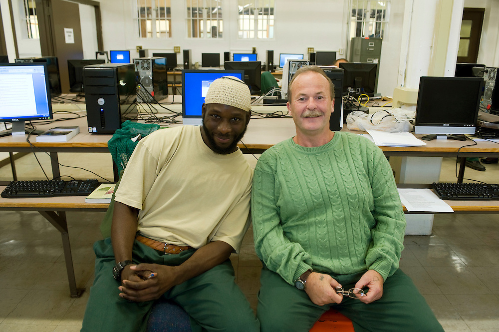 """Woodbourne Correctional Facility inmate and Bard College student Abdullah Kamau Sankofa (left) studies in the computer room. He has been sentenced to 18 years in prison at the age of 17. He graduated from Bard College with fellow inmate Carlos Rosario in May 2010. (Book: The Coming of the French Revolution) Bill Doane (55) is one of his mentors...Story: The Bard Prison Initiative.Former inmate Carlos Rosario, 35-year-old husband and father of four, was released from Woodbourne Correctional Facility after serving more than 12 years for armed robbery. Rosado is one of the students participating in the Bard Prison Initiative, a privately-funded program that offers inmates at five New York State prisons the opportunity to work toward a college degree from Bard College. The program, which is the brainchild of alumnus Max Kenner, is competitive, accepting only 15 new students at each facility every other year. .Carlos Rosario received the Bachelor of Arts degree in social studies from the prestigious College Saturday, just a few days after his release. He had been working on it for the last six years. His senior thesis was titled """"The Diet of Punishment: Prison Food and Penal Practice in the Post-Rehabilitative Era,"""".Rosado is credited with developing a garden in one of the few green spaces inside the otherwise cement-heavy prison. In the two years since the garden's foundation, it has provided some of the only access the prison's 800 inmates have to fresh vegetables and fruit...Rosario now works for a recycling company in Poughkeepsie, N.Y...Photo © Stefan Falke"""