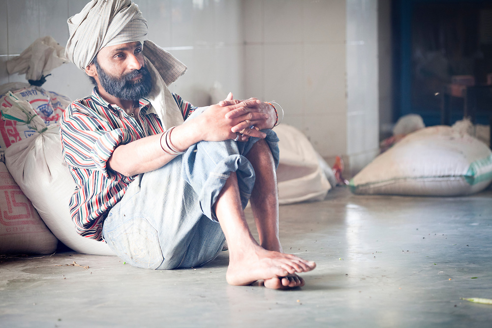 A volunteer cooks in a Sikh kitchen taking a short break.The Sikh kitchen provides ten of thousands of free meals on a daily basis.