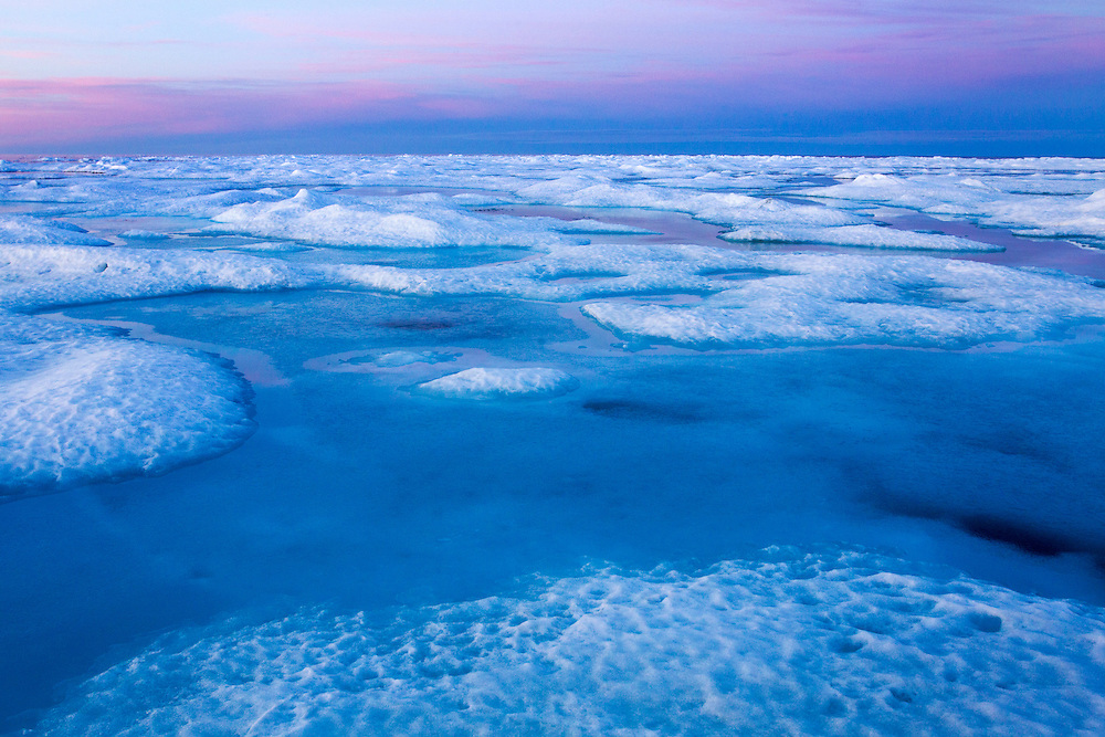 Canada, Manitoba, Churchill, Midnight sun lights cirrus clouds above melting ice on Hudson Bay