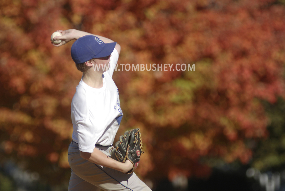 Middletown, N.Y. -  The changing colors of a maple tree in the background are visible as pitcher winds up during a fall recreational baseball league at Watts Park on Oct. 21, 2007.