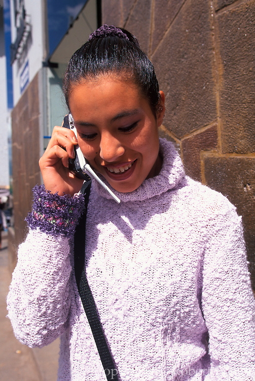 PERU, HIGHLANDS, CUZCO ancient capital of the Incas; a Peruvian student using a cel phone in the center of the city near the university