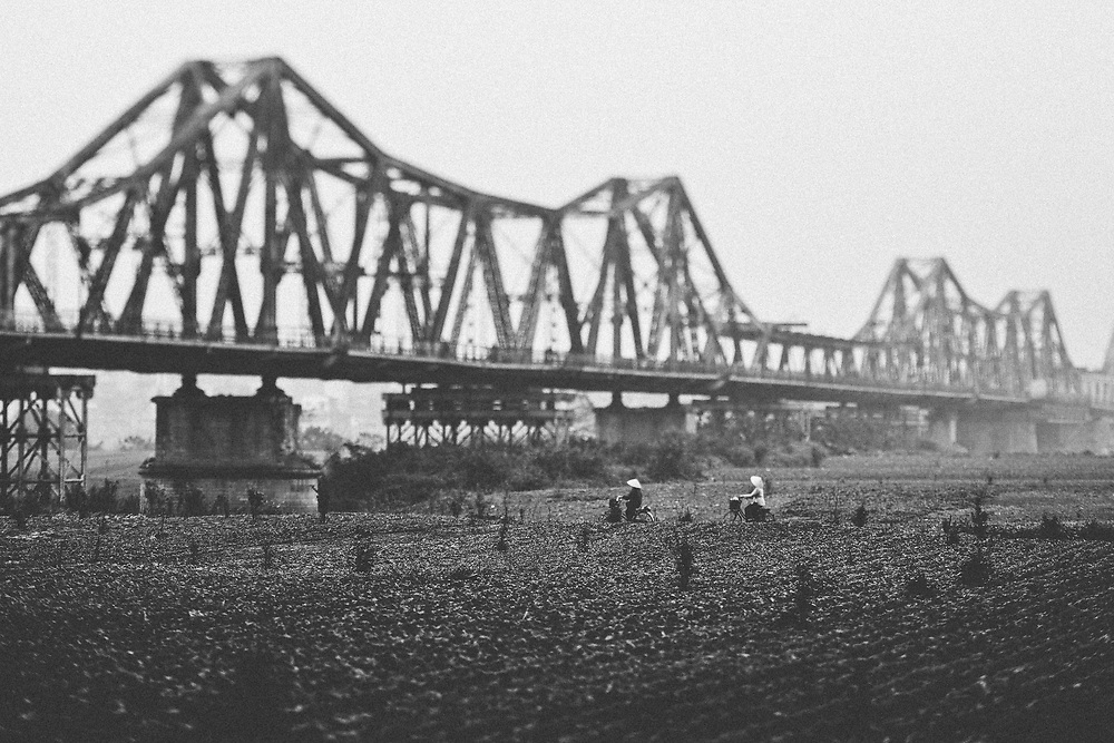 A view of Long Bien Bridge and the surrounding countryside in Hanoi, Vietnam. The historic structure was built in 1903 and remains an important landmark in the capital, despite its crumbling pillars and rusting rails.