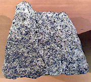 Granite - is a common and widely occurring type of intrusive, felsic, igneous rock.  Granite usually has a coarse-grained texture.  Occasionally some individual crystals are larger than the groundmass, in which case the texture is known as porphyritic.