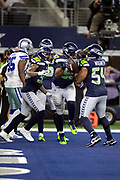 Seattle Seahawks outside linebacker K.J. Wright (50) celebrates with Seahawks middle linebacker Bobby Wagner (54) and teammates after intercepting a fourth quarter pass that stops a Cowboys drive at the Seahawks 16 yard line during the NFL football NFC wild card playoff game against the Dallas Cowboys on Saturday, Jan. 5, 2019 in Arlington, Tex. The Cowboys won the game 24-22. (©Paul Anthony Spinelli)