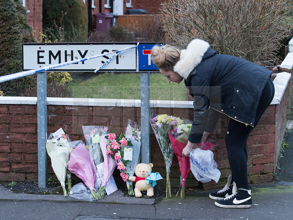 © Licensed to London News Pictures . 11/02/2014 . Blackburn , UK . A woman leaves flowers at the scene . Police and forensic examiners on Emily Street in Blackburn at the scene where an eleven month old baby girl was mauled to death late last night (10th February 2014) . Photo credit : Joel Goodman/LNP