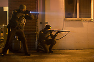 Police draw their weapons on suspected looters in an alley in Dellwood, Mo., on Monday, November 24, 2014. The area erupted in unrest moments after a grand jury returned a decision not to indict Ferguson Police Officer Darren Wilson in the August shooting death of unarmed teenager Michael Brown, Jr.