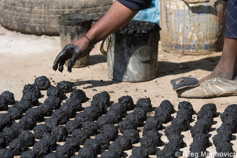 Mankepane Ntsoereng works clay and coal dust into coal bricks for cooking in Boiketlong. The trickle of water from her closest standpipes and the long queue means her vegetable garden is not thriving  Residents of the informal settlements that dot the Sebokeng/Evation area south of Johannesburg have been taking to the streets to protest lack of service delivery, or inadequate services that are not what they believe were promised them by the African National Congress before they came into power in 1994. August 24, 2007. Photo Greg Marinovich