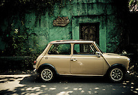 A mini cooper sits parked in front of a green wall in Seminyak, Bali, Indonesia.