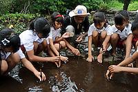 Bapak Juanda Datundugon helping children to plant mangrove seedlings during an environmental education class, Dudepo, Bolmong Selatan, Sulawesi, Indonesia.