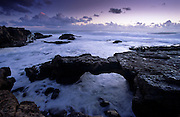 As the tide becomes higher, the water starts flowing under a rock arch formation near Cape Raso