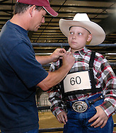 NEWS&GUIDE PHOTO / PRICE CHAMBERS.Ryder gets some fatherly attention from Kevin before showing one of his steers at the Teton County Fair. The family is upset about the lack of support from 4-H. Regarding the rules of the animals' care, no exceptions were made for the sick child.