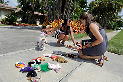 31 July 2015. Marco Island, Florida.<br /> L/R;  Protesters Gianna Solarte (a dentist) and Daniella Melo (a vet) put down stuffed animals spelling out the word 'KILLER' outside the deserted Florida home of Dr Walter Palmer. Palmer is the Minnesota dentist who allegedly killed Cecil the lion in Zimbabwe. Dr Palmer has gone to ground since the story broke, taking him from hunter to hunted.<br /> Photo; Charlie Varley/varleypix.com