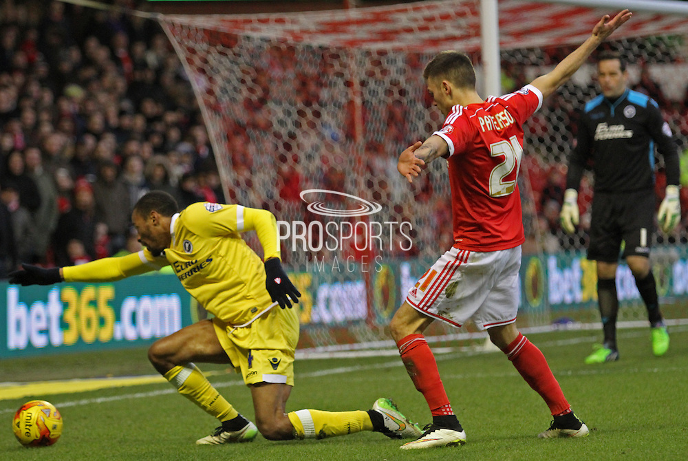 Shaun Cummings is fouled by Jamie Paterson during the Sky Bet Championship match between Nottingham Forest and Millwall at the City Ground, Nottingham, England on 31 January 2015. Photo by Jodie Minter.