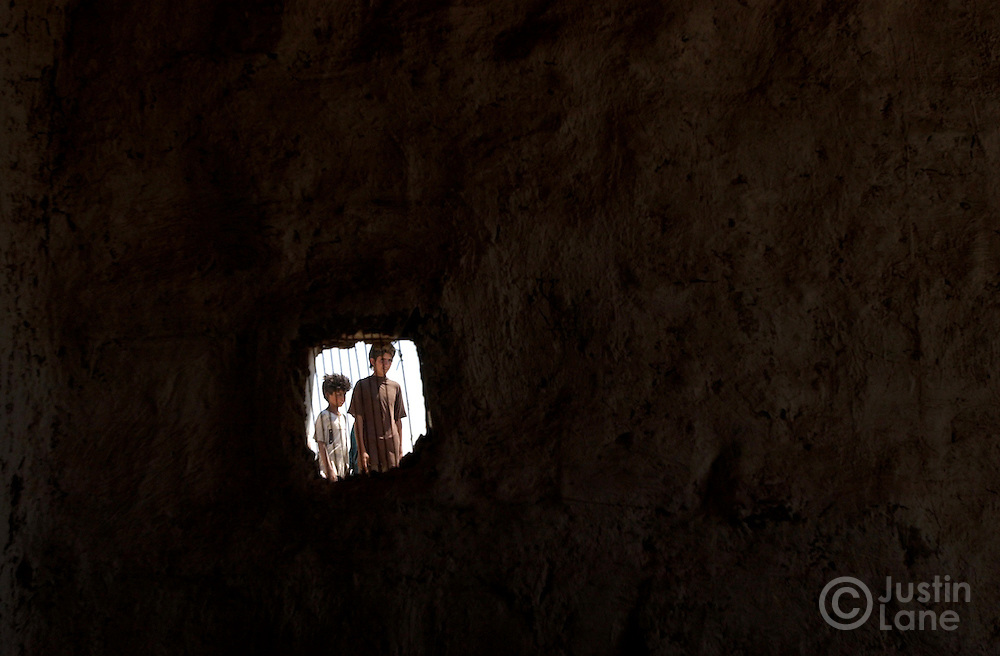 Two children who live in a garbage dump outside of Baghdad are seen through a small window of their home.