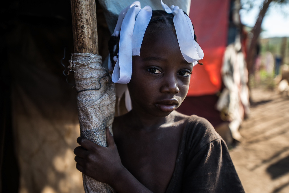ANSE-A-PITRE, HAITI - NOVEMBER 23, 2015: 5-year old Gernite Jean poses for a portrait outside of her family's tent in Camp Cadeau 2, one of five camps where approximately 4,000 people have arrived since the spring, who by force or fear left the Dominican Republic after the government began a crackdown on illegal migrants and those without paperwork to support their residence.  She was born in the Dominican Republic, on a bean farm where her parents worked, but her family self-deported to the border camps in Haiti last June after being threatened to be deported. She said she would rather live in the Dominican Republic than in Haiti, because at her old home, there was more food, and there wasn't so much dust.  PHOTO: Meridith Kohut for The New York Time3