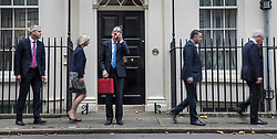 © Licensed to London News Pictures. 22/11/2017. London, UK. Chancellor of the Exchequer Philip Hammond holds his red ministerial box for photographers as (L-R) Andrew Barclay, Economic Secretary, Liz Truss, Chief Secretary, Mel Stride, Financial Secretary and Andrew Jones, Exchequer Secretary walk past Number 11 Downing Street on budget day. Photo credit: Peter Macdiarmid/LNP
