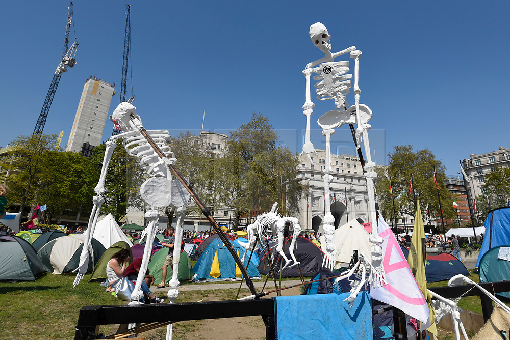 "© Licensed to London News Pictures. 22/04/2019. LONDON, UK. Fake skeletons made by activists gathered at Marble Arch during ""London: International Rebellion"", on day eight of a protest organised by Extinction Rebellion.  Protesters are demanding that governments take action against climate change.  After police issued section 14 orders at the other protest sites of Oxford Circus, Waterloo Bridge and Parliament Square resulting in over 900 arrests, protesters have convened at the designated site of Marble Arch so that the protest can continue.  Photo credit: Stephen Chung/LNP"