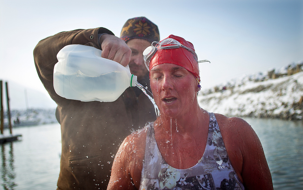 Sue Frehse has warm water poured over her back after finishing the New Year's Day Open Water Race at the Great Salt Lake Marina, Tuesday, Jan. 1, 2013. The members of the Wasatch Front Polar Bear Club have been training throughout the winter to prepare them for the 400 meter race through frigid water.
