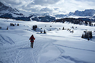 A woman walking on a snow trail in the Alpe di Siusi Ski resort near the town of Otisei in the Dolomites, Italy