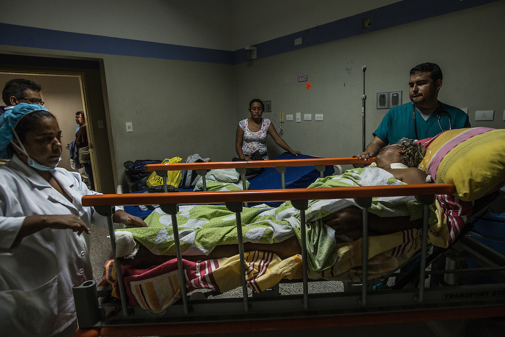 PUERTO LA CRUZ, VENEZUELA - APRIL 15, 2016: Dr. Freddy Diaz (right) moves Rosa Parucho, a diabetic patient in septic shock from an upper floor of the hospital to the emergency room.  Doctors were limited in how they could care for her, because they don't have a dialysis machine, nor the antibiotics that she requires. Ms. Parucho contracted an infection while in the hospital, that spread to her feet, which had now turned black and doctors said require amputation.  Hospital Universitario Dr. Luís Razetti is one of the worst state-run, public hospitals in Venezuela.  Doctors compare it to working in a war zone - they regularly have to turn patients away, because they don't have the majority of medicines  or medical equipment and supplies needed to give them medical attention.  When they do accept patients, they have to work with extremely limited resources, because they don't have the supplies they need for things like X-Rays,  and many exams nd operations.  The hospital's infrastructure is crumbling, and staff don't have all the cleaning supplies required to keep the hospital sanitary. The hospital also suffers from weekly shortages of running water and electricity.  In April, several babies died when a power outage turned off the incubators, and the hospital's generator failed to work because of lack of maintenance.  The same month, authorities found over 100 pieces of medical equipment, stolen from the hospital in the home of the assistant to the hospital's director.  Despite having the largest oil reserves in the world, falling oil prices and wide-spread government corruption have pushed Venezuela into an economic crisis, with the highest inflation in the world and chronic shortages of food and medical supplies. PHOTO: Meridith Kohut