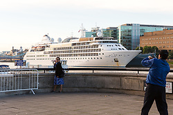 © Licensed to London News Pictures. 01/08/2017. LONDON, UK.  Tourists take a photograph in front of Silver Wind, a huge 514 feet long, 17,400 ton cruise liner seen moored next to HMS Belfast before she leaves London under Tower Bridge this morning after a brief visit, towed backwards by two tugs. Silver Wind carries just 296 passengers and its owner, Silversea claim that the ship has amongst the highest space-to-guest ratios in the cruise ship industry, with the largest suites measuring 1,314 square feet. Tickets cost thousands of pounds, but all guest expenses, even champagne are included in the price. Environmentalists claim thepollutioncreated by giantcruise ships outweigh their economic benefits. The Port of London Authority (PLA) are conducting a work programme during 2017 to monitor air quality and pollution caused by river traffic on the River Thames.  Photo credit: Vickie Flores/LNP