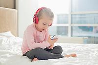 Full length of girl listening music on headphones in bedroom