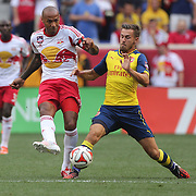 Thierry Henry, (left), Arsenal, passes while challenged by Aaron Ramsey, Arsenal, during the New York Red Bulls Vs Arsenal FC,  friendly football match for the New York Cup at Red Bull Arena, Harrison, New Jersey. USA. 26h July 2014. Photo Tim Clayton