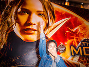 20 NOVEMBER 2014 - BANGKOK, THAILAND: NATCHACAH KONG-UDOM displays the three fingered salute from the Hunger Games movies in front of a Hunger Games poster in the lobby of the Siam Paragon movie theaters. She was one of at least three people arrested by Thai police during the opening the Hunger Games: Mockingjay - Part 1 in Bangkok Thursday. Opponents of the Thai military coup have adapted the three fingered salute used in the Hunger Games series as a sign of their opposition to the coup. In the weeks before the movie opening Thai police arrested several people for using the Hunger Games salute and Thai media reported that one Thai movie theater chain cancelled plans to show the movie at the request of the military government. There were several small protests at theaters showing the movie Thursday.     PHOTO BY JACK KURTZ