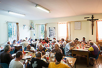 ROME, ITALY - 26 AUGUST 2016: Homeless men have dinner in the soup kitchen of Casa Serena, a prefabricated house for homeless men in Rome, Italy, on August 26th 2016.<br /> <br /> Casa Serena, inaugurated in 1993, hosts approximately 70 men, 50 years or above, of any nationality, religion, colour. <br /> <br /> The Missionaries of Charity-Contemplative is a diocesan religious Institute composed of Brothers and priests with equal rights and obligations, founded by Blessed Teresa of Calcutta with Fr. Sebastian Vazhakala in 1979. The members take public vows of Chastity, Poverty, Obedience and free service to the poor.<br /> <br /> Mother Teresa, also known as Blessed Teresa of Calcutta, was an Albanian Roman Catholic nun and missionary. She founded the Missionaries of Charity, a Roman Catholic religious congregation, whose members must adhere to the vows of chastity, poverty, and obedience, as well as the vow to give wholehearted free service to the poorest of the poor. Shortly after she died in 1997, Pope John Paul II waived the usual five-year waiting period and allowed the opening of the process to declare her sainthood. She was beatified in 2003. A second miracle was credited to her intercession by Pope Francis, in December 2015, paving the way for her to be recognised as a saint by the Roman Catholic Church. Her canonisation is scheduled for September 4th 2016, a day before the 19th anniversary of her death.